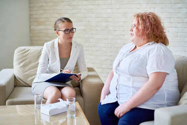 Portrait of obese young woman opening up to female psychiatrist during therapy session  on mental issues
