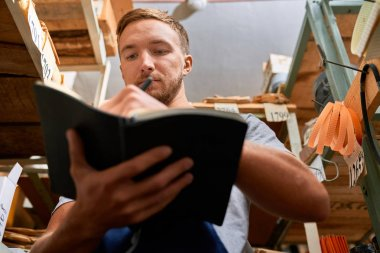 Low angle portrait of young man holding stock journal and making notes while doing inventory in tools store
