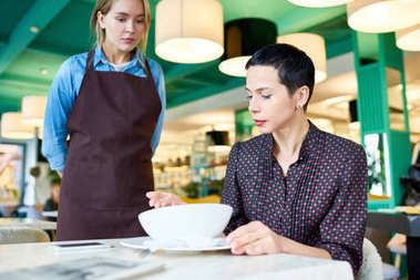 Portrait of elegant woman  complaining about food quality and taste to young waitress in cafe