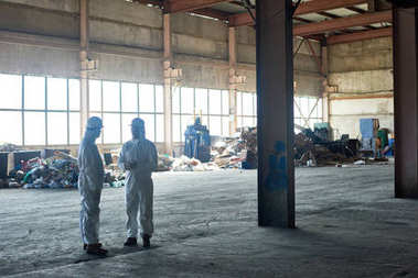 Tam uzunlukta portre ambar giyen iki işçilerin atık işleme tesisi, arka planda, kopya alanı çöp yığınları boş atölye ayakta uygun