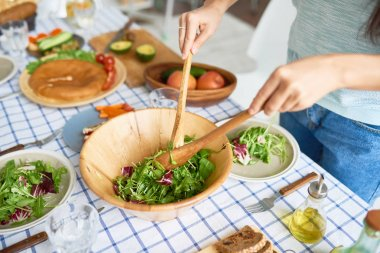 Closeup of young woman mixing green salad in wooden bowl at table with wholesome food while preparing family dinner in kitchen