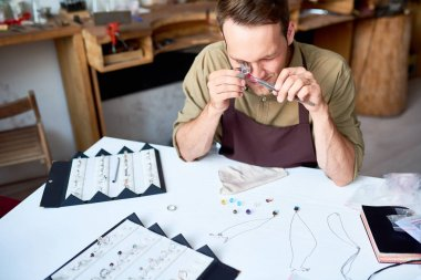 Portrait of young man inspecting jeweler with magnifying glass while appraising goods in pawn shop