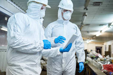 Portrait of two workers  wearing biohazard suits and protective masks using digital tablet  at waste processing plant , copy space