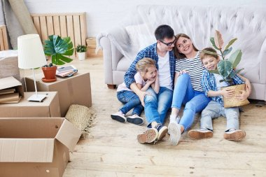 Full length portrait of loving young family gathered together in living room of new apartment and sharing ideas concerning interior design, cute little boy holding houseplant in hands