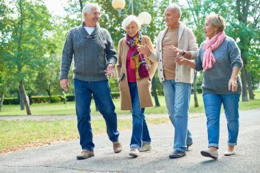 Portrait of two senior couples going for walk in park and smiling happily chatting on the way enjoying sunny autumn day