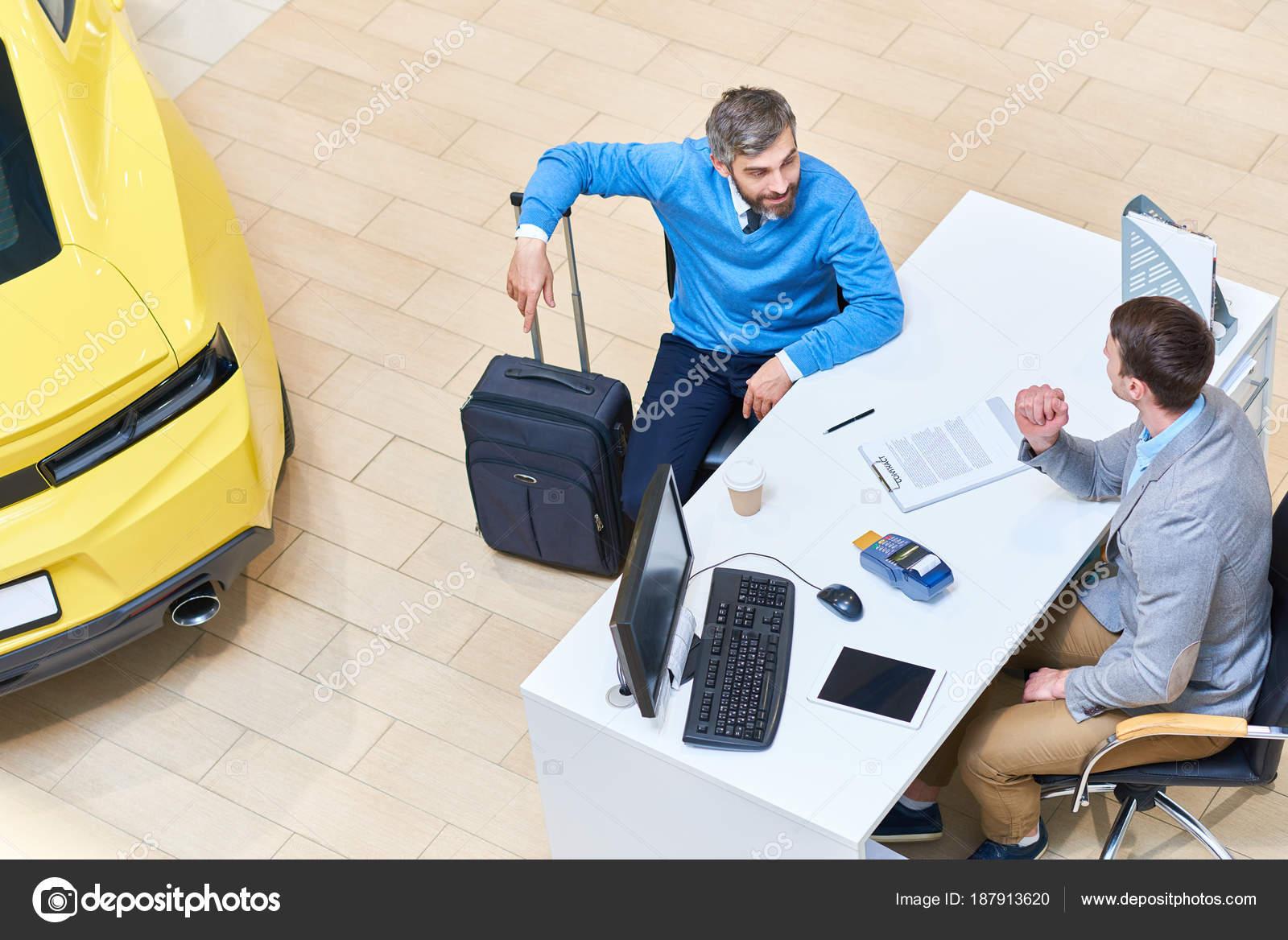 Dessus homme mature parler vendeur voiture assis bureau magasin