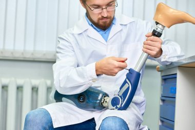 Portrait of bearded technician checking artificial limb while sitting at desk in office, adjusting it and checking for quality
