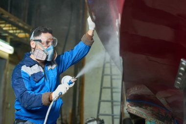 Side view portrait of worker wearing protective mask spray painting boat in yacht workshop