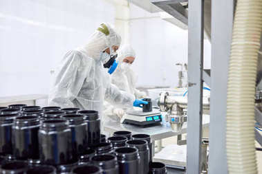 Group of workers wearing coveralls and respirators using electronic scale in order to weigh bottle with pills, interior of modern pharmaceutical factory on background
