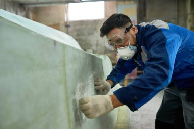 Side view portrait of worker wearing protective mask repairing boat while working in yacht workshop