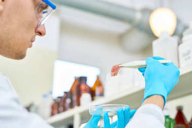 Close-up shot of confident young scientist wearing safety goggles and rubber gloves checking quality of artificial meat grown in modern laboratory