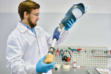 Portrait of young prosthetic's technician holding prosthetic leg checking it for quality and making adjustment while working in modern laboratory