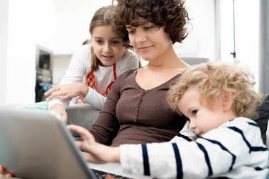 Portrait of young mother using laptop with two children looking at screen while searching internet at home