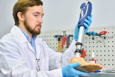 Portrait of young  prosthetist holding prosthetic leg checking it for quality and making adjustment while working in modern laboratory