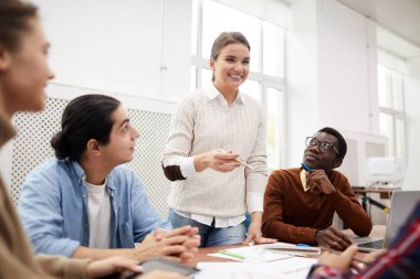 Multi-ethnic group of students working together on team project while studying in college, focus on smiling girl heading meeting