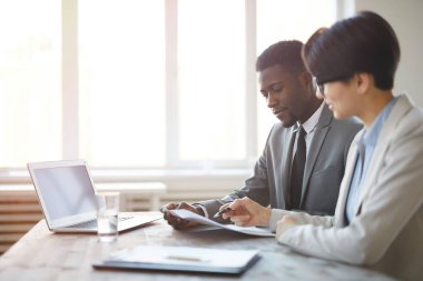 Side view portrait of young African businessman reading documents with female colleague while sitting at workplace against window in office, copy space