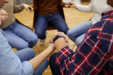 High angle close up of unrecognizable people sitting ion circle and holding hands during support group meeting, cpy space