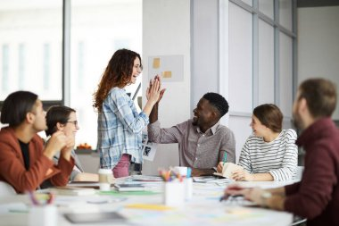 Portrait of creative business team giving high five while planning project during meeting in office, focus on smiling young woman standing by table
