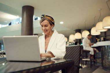 Portrait of mature woman smiling happily while using laptop in restaurant at luxury SPA resort, copy space