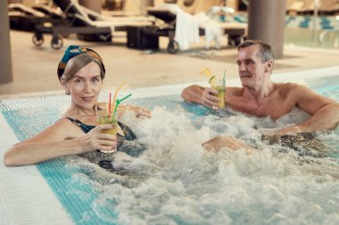 High angle portrait of modern senior couple relaxing in bubbly hot tub and drinking cocktails at luxury SPA resort, copy space