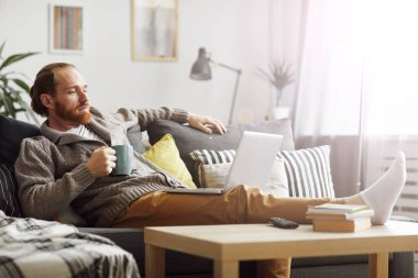 Full length portrait of bearded man watching videos via laptop and drinking coffee while relaxing on comfortable couch at home, copy space