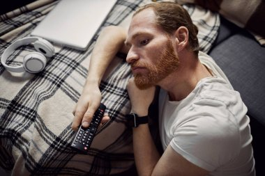 High angle view at adult man sleeping on sofa while watching TV at night, copy space