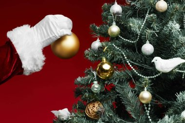 Close up of Santa Claus hanging golden ornament on Christmas tree standing against red background, copy space