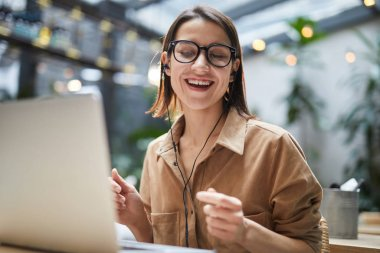 Portrait of carefree young woman listening to music while working in outdoor cafe and dancing, copy space