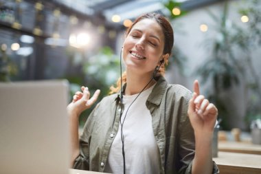 Portrait of carefree young woman listening to music while working on cafe terrace and dancing, copy space