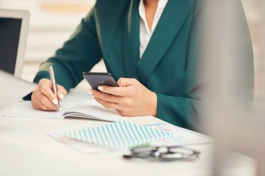 Close up of unrecognizable businessman using smartphone during business meeting in office, copy space