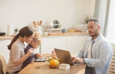 Side view portrait of modern father using laptop while enjoying family breakfast in cozy kitchen interior