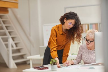 Horizontal shot of two female clothes designers working together on new fashion collection
