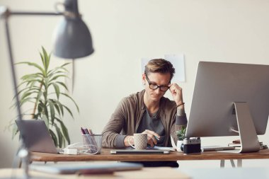 Portrait of contemporary businessman working in office, adjusting glasses and reading documents at wooden desk, copy space