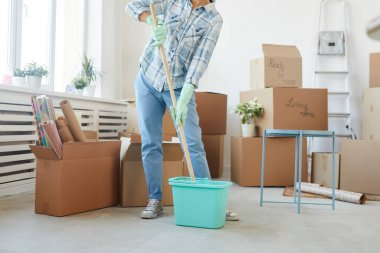 Low section portrait of happy young woman cleaning new house or apartment while moving in, copy space