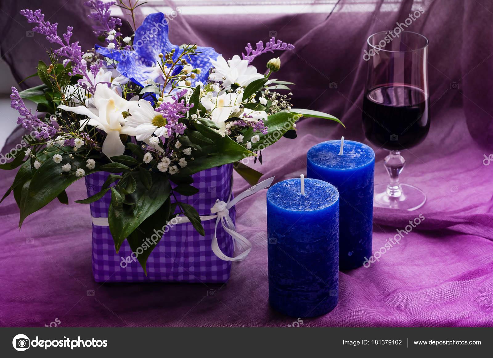 e5cc02e087d ανθοδέσμη από ανοιξιάτικα λουλούδια και μπλε κεριά με ένα ποτήρι ...