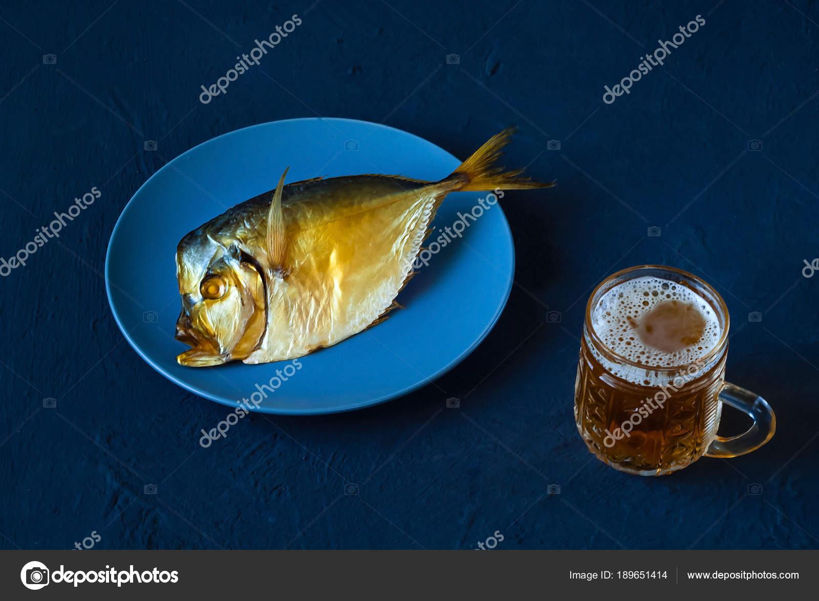 Pesce Affumicato Su Un Piatto Blu E Birra In Un Calice Di Vetro Su