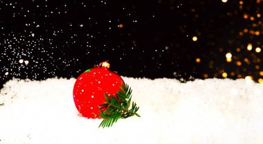 Christmas decorations on snow texture on black background with sparkles. Blurry effect. Copy space