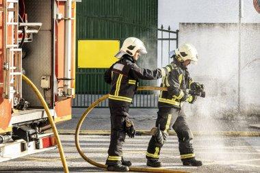 Yangın söndürmek için su hortumuyla su çeken itfaiyeciler.