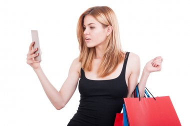 Beautiful girl holding shopping bags browsing on smartphone