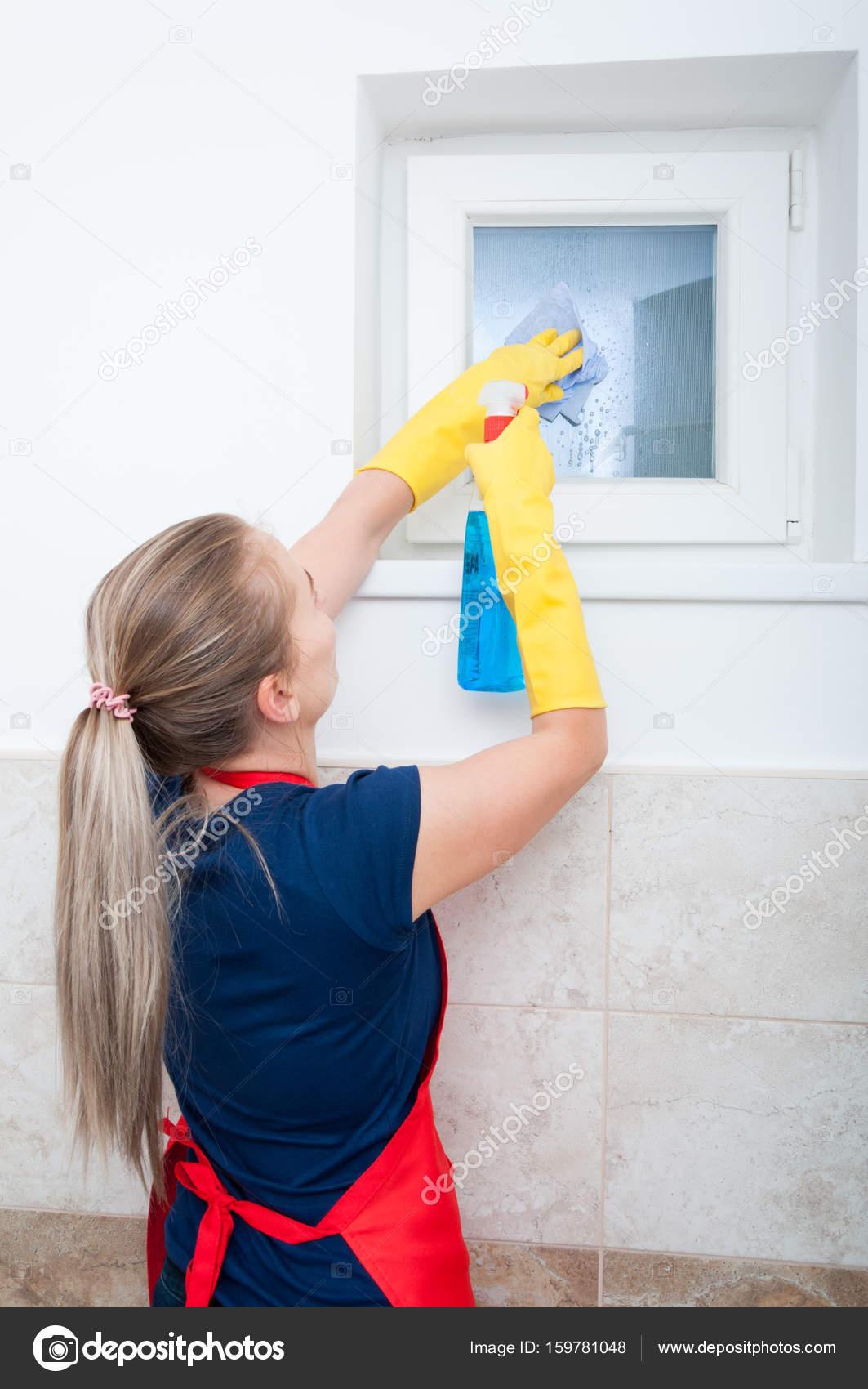 Donna che pulisce la finestra del bagno con spray di pulizia — Foto ...