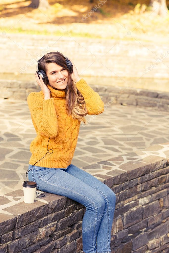 Beautiful fashion model relaxing in fall park outdoors
