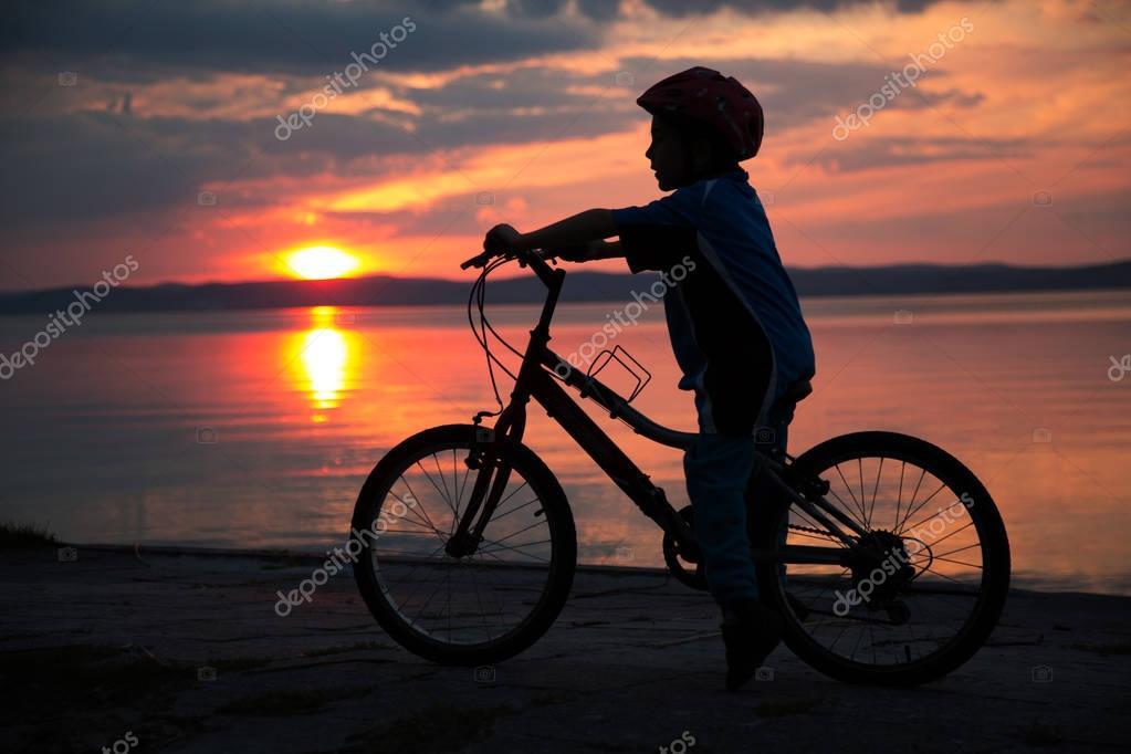 Silueta De Un Muchacho Joven, En La Puesta De Sol, Montar