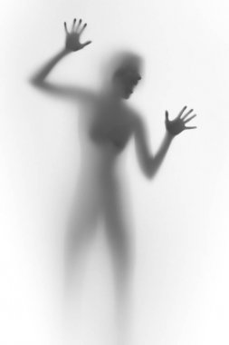Imprisioned woman behind a glass wall, shouts. Face, silhouette, hands.
