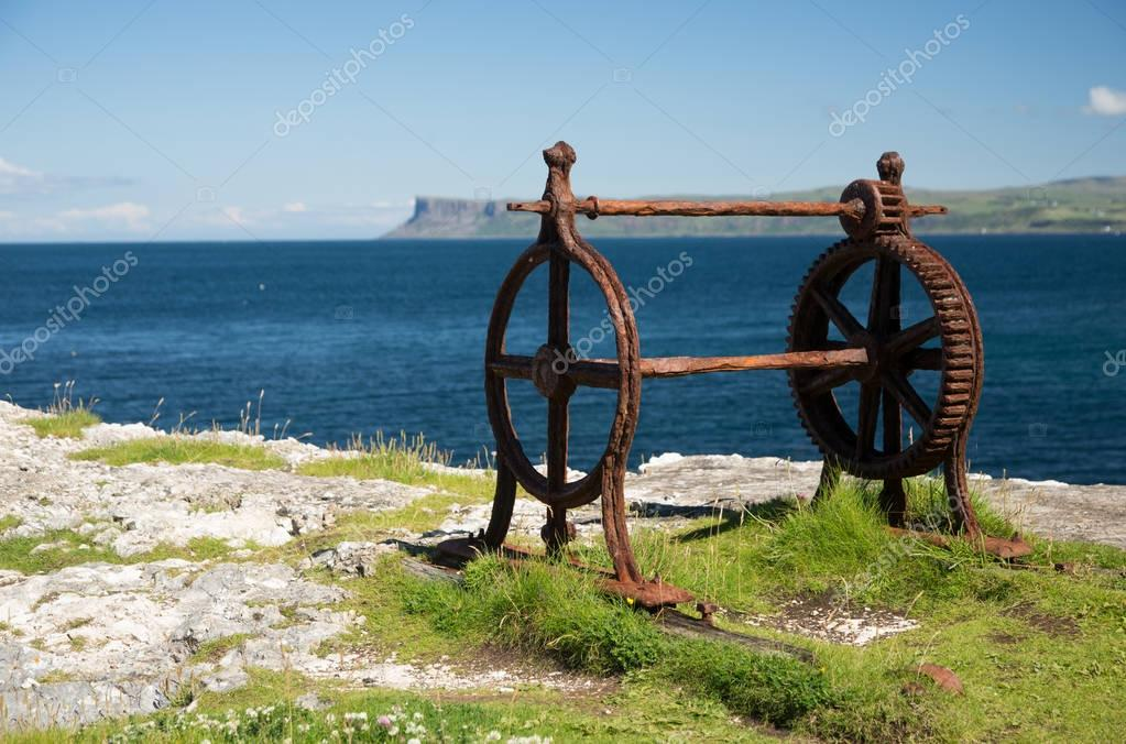 Old corroded iron winder with cogwheel, next to the sea, irish coast