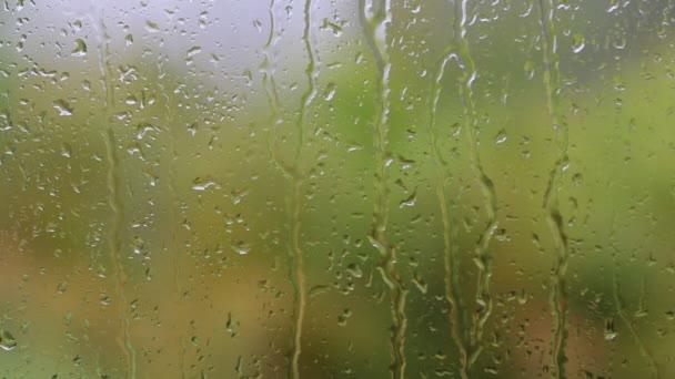 Tropický den deštivý podzim. Dešťové kapky na sklo okna domu. Zaměřit se na dešťové kapky stékající po okna, velké zelené palmového listí rozmazaným pozadím. Ostrov Koh Phangan, Thajsko