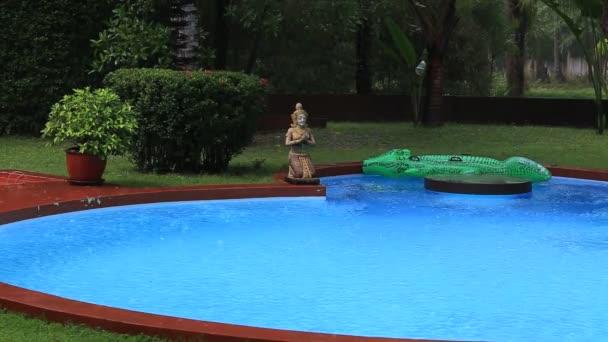 Tropický letní déšť padá velké deště klesá klesá na bazén s tropickými stromy v Thajsku