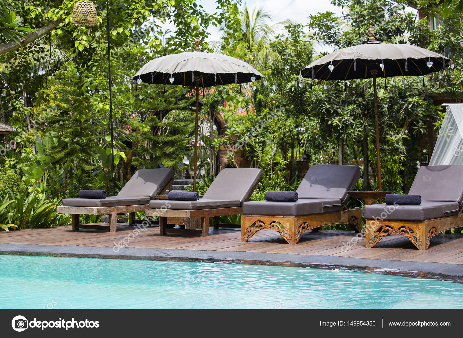 Swimming pool and deck chairs in tropical garden. Island ...