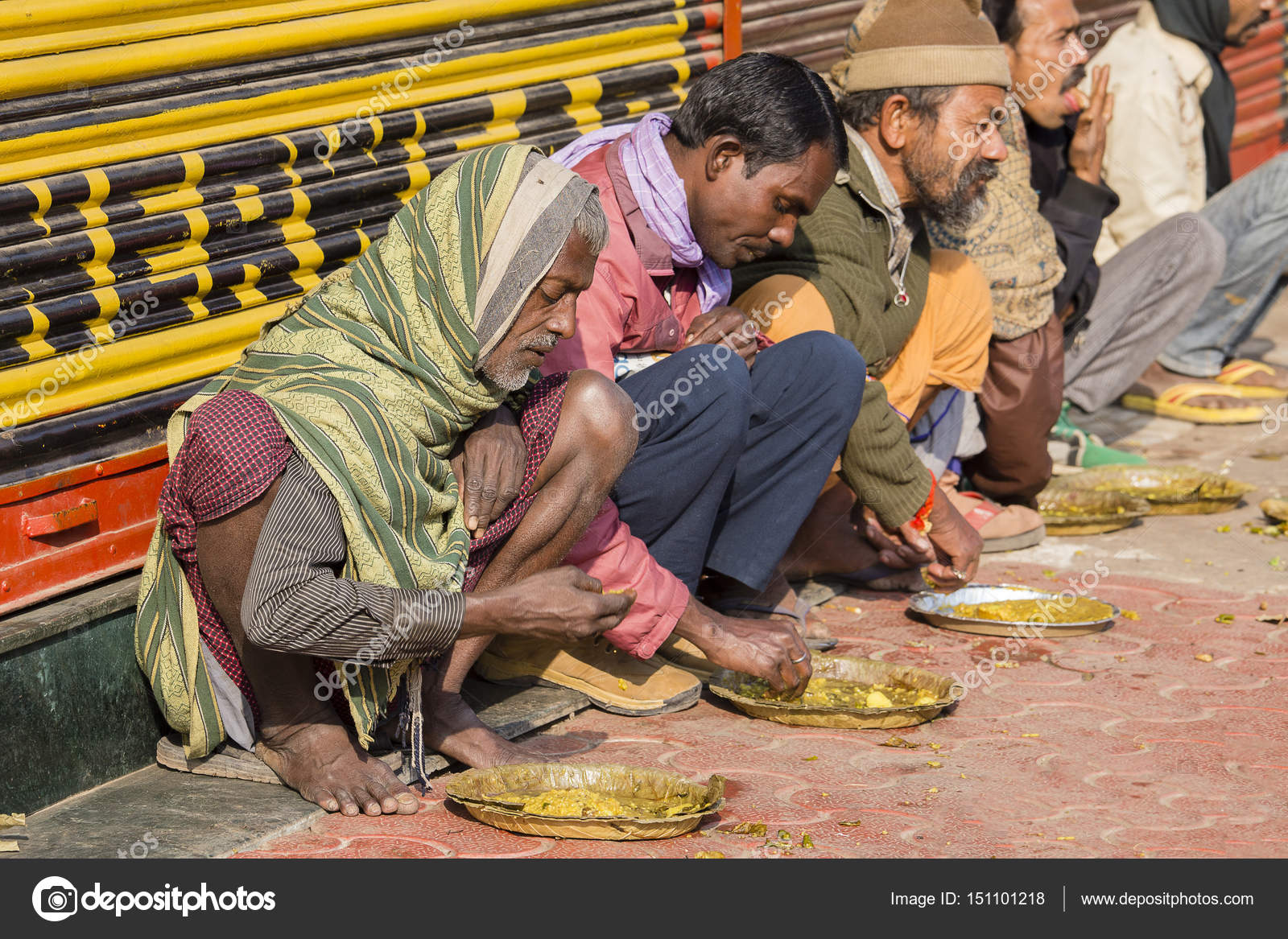 poor indian people eating free food at the street in