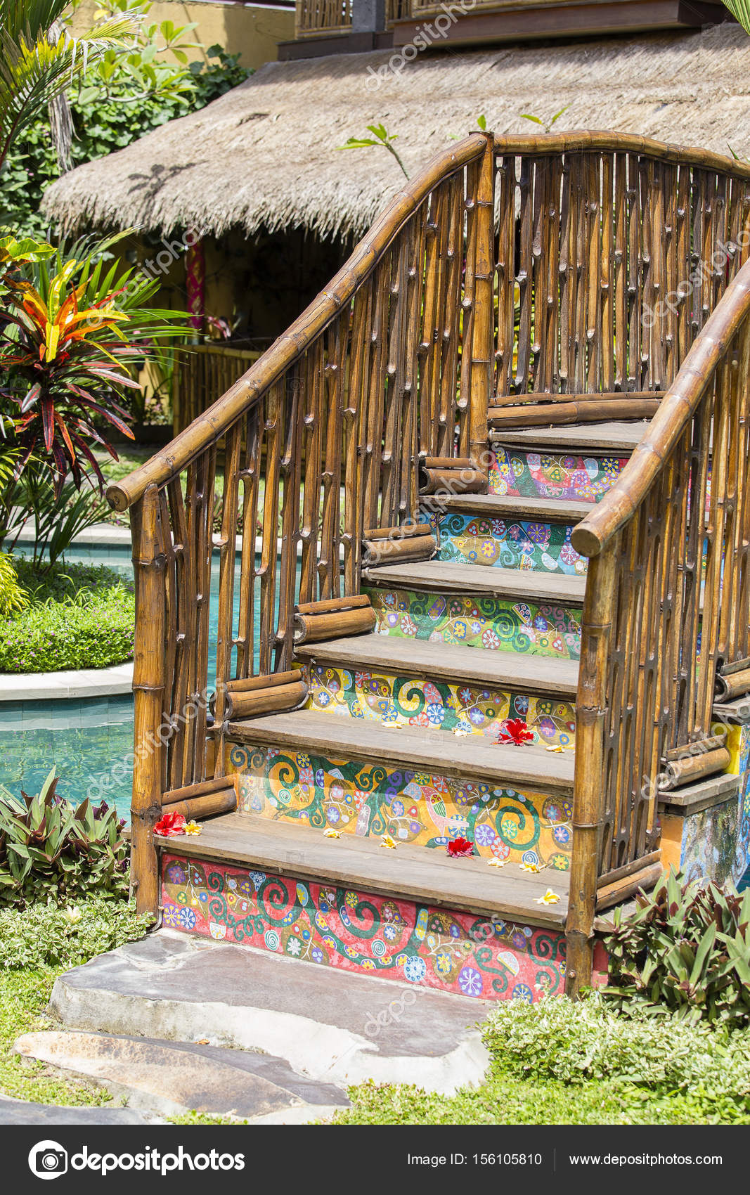 Colorful wooden bridge in a tropical garden next to the swimming ...