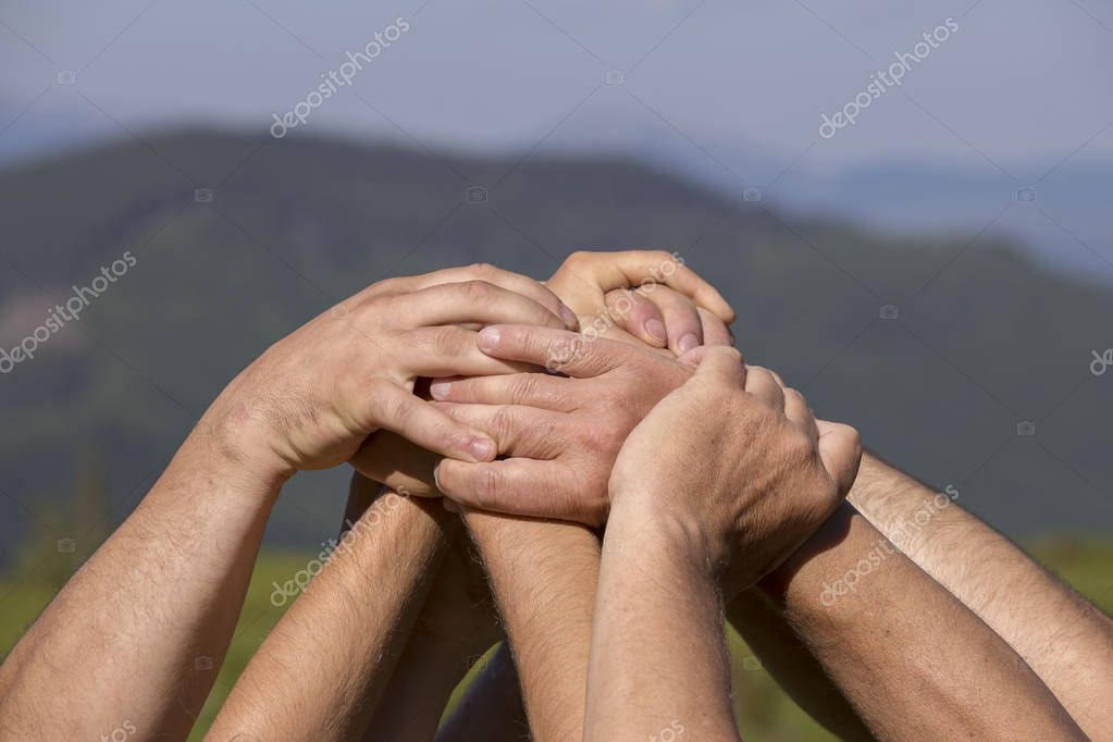 Successful team: many hands holding together on nature background